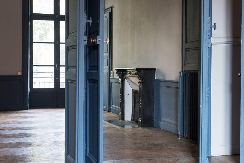 Défiscalisation immobilière. Salon intérieur non meublé, fausse cheminée et grande fenêtre