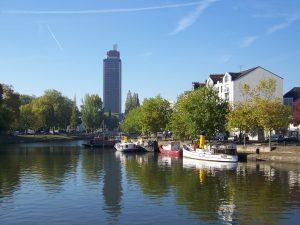 Prix immobilier Nantes. Fleuve avec bateaux et grand immeuble en arrière plan