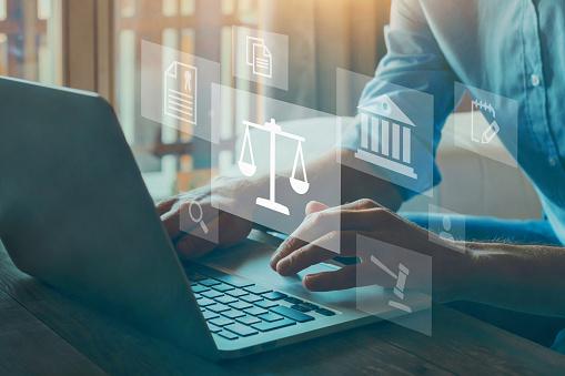loi Pinel 2021. Des doigts sur un clavier d'ordinateur, dessin de la balance juridique.