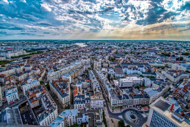 Nantes Ouest Immobilier. Vue aérienne de Nantes, ciel ensoleillé mais nuageux. Couché de soleil