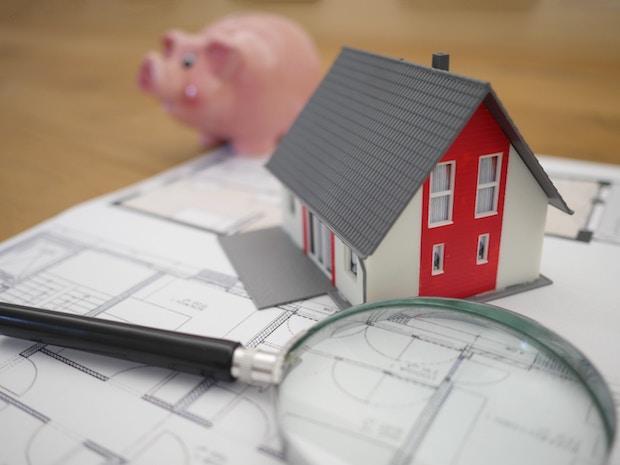 Investissement locatif Nantes. Un plan poser sur une table avec dessus une loupe, une petite maquette de maison et en arrière plan un cochon