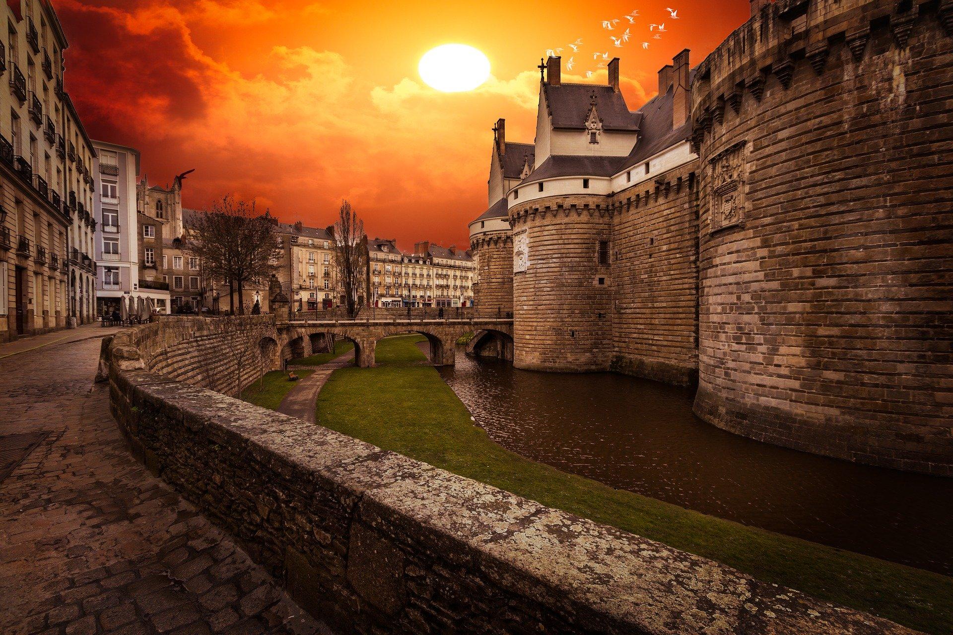 marché immobilier nantes. Extrémité gauche du château avec des immeubles et un couché de soleil orange