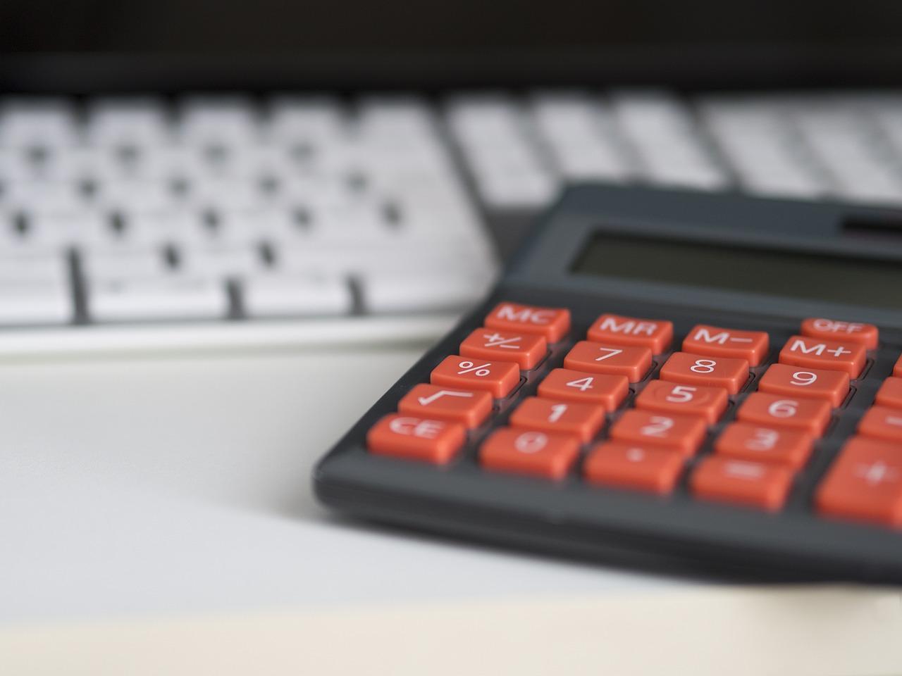 Rentabilité locative. Calculatrice noir et rouge posée à côté d'un clavier